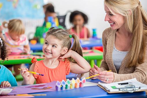 Dziewczynka w przedszkolu siedzi przy stole ze swoją nauczycielką i maluje kolorowymi farbami patrząc na kogoś w górę.