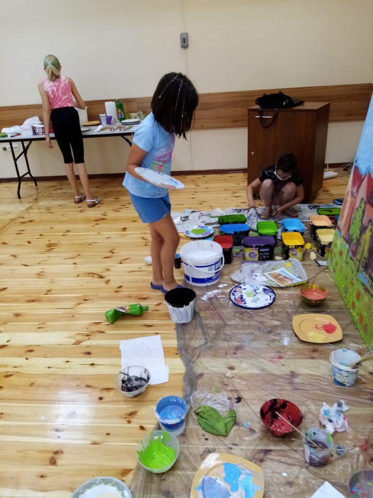 Dziewczyny podczas prac malarskich, otoczone farbami w puszkach, które rozłożone są na folii zabezpieczającej podłogę