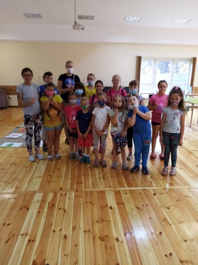 Pamiątkowe zdjęcie grupy dzieci wraz z panią instruktor w pomieszczeniu GOK Herby, w któyrm przygotowywany był mural